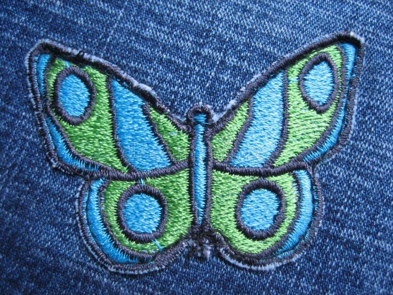Farfalla sui jeans immagine stock