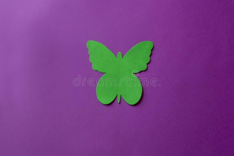 Farfalla verde fatta di materiale molle su un fondo viola Farfalla artificiale su fondo luminoso fotografia stock libera da diritti