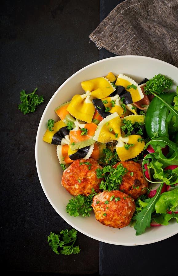 Farfalle面团硬质小麦用鸡内圆角被烘烤的丸子在西红柿酱和沙拉的 图库摄影