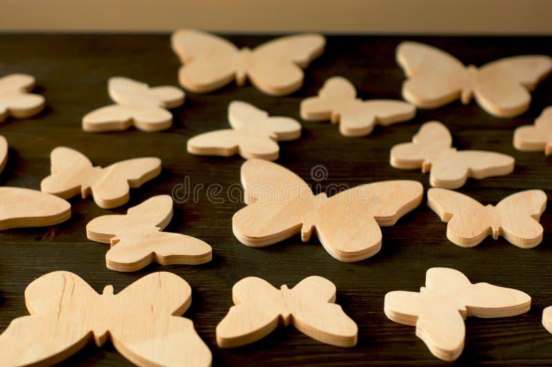 Farfalle di legno su un fondo di legno nero fotografia stock libera da diritti
