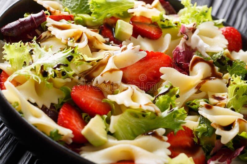 Farfalle pasta med avokadot, jordgubbar, blandninggrönsallat och balsamic klä närbild på en platta horisontal royaltyfri foto