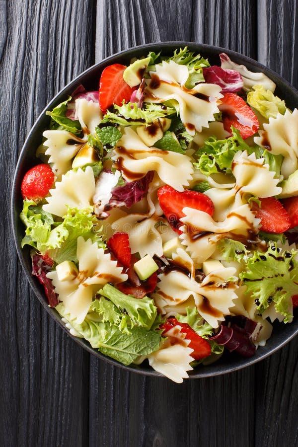 Farfalle pasta med avokadot, jordgubbar, blandninggrönsallat och balsamic klä närbild på en platta Vertikal b?sta sikt arkivfoto