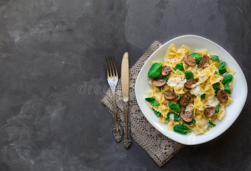 Farfalle pasta med champinjoner och spenat royaltyfri fotografi
