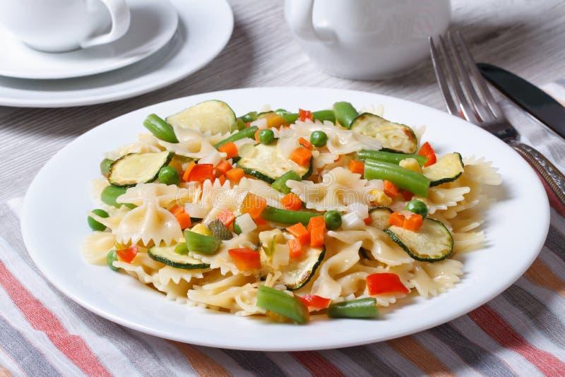 Farfalle pasta med skivor av grönsaker, ostcloseup arkivbilder