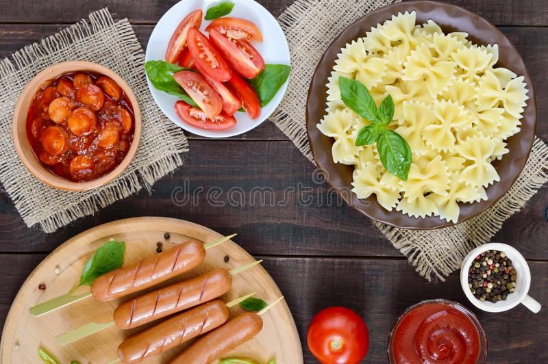 Farfalle pasta, sausages on skewers, fresh tomatoes, spicy tomato sauce royalty free stock image
