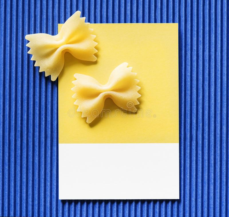 Farfalle pasta on a yellow card stock photos