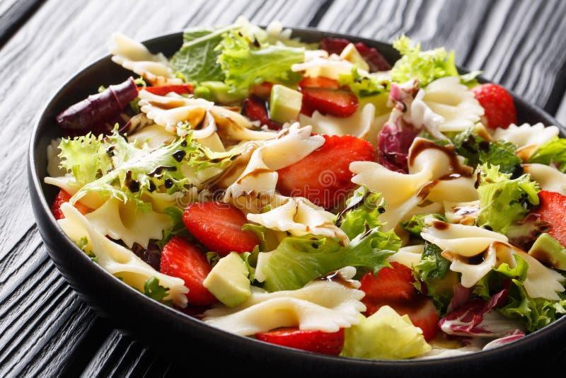 Farfalle régénérateur de salade de pâtes avec l'avocat, les fraises, la laitue et le plan rapproché balsamique de sauce horizonta image libre de droits