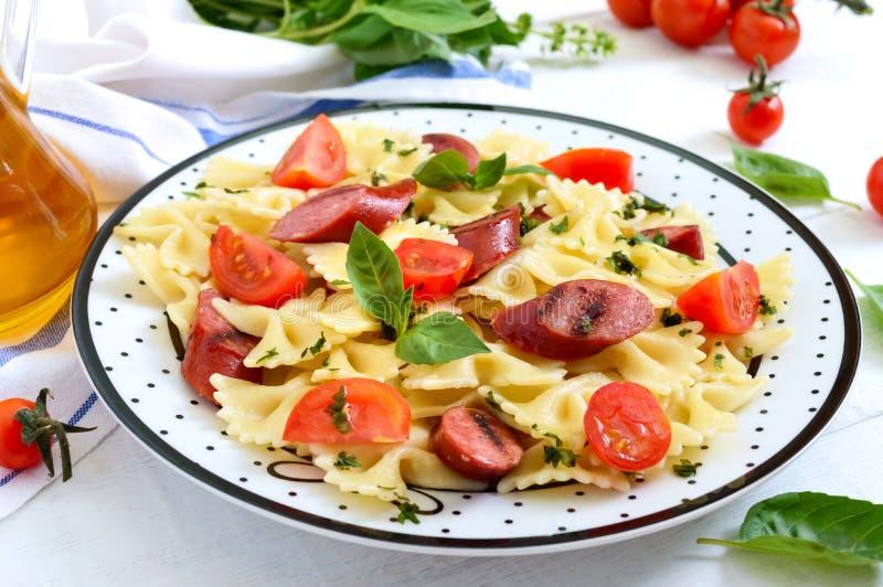 Farfalle saporito della pasta con le salsiccie arrostite, i pomodori ciliegia freschi ed il basilico su un piatto su un fondo di  immagini stock