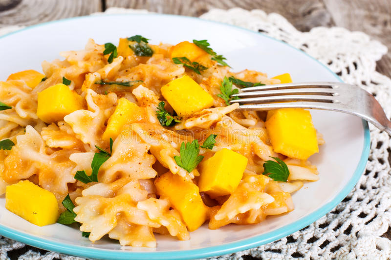 Farfalle with slices of pumpkin and parsley stock photography