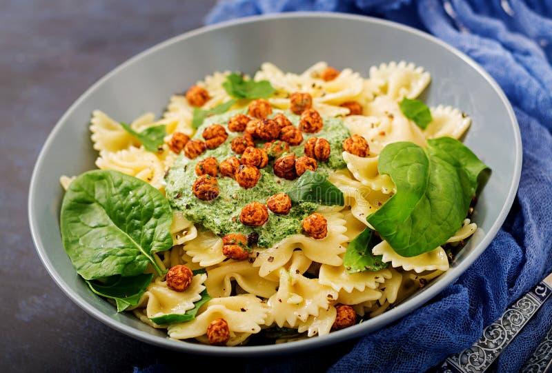 Farfalle-Teigwaren des strengen Vegetariers mit Spinatssoße mit gebratenen Kichererbsen lizenzfreies stockbild