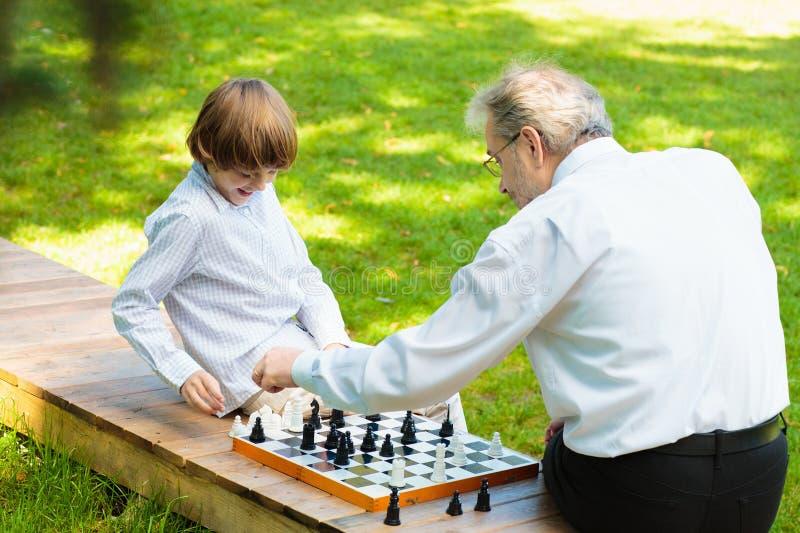 Farfar, fader och ungar som spelar schack arkivfoto