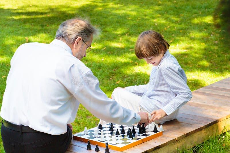 Farfar, fader och ungar som spelar schack royaltyfria foton