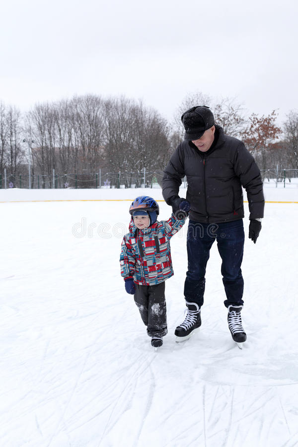 Farfar med barnbarnet på den åka skridskor isbanan arkivfoton