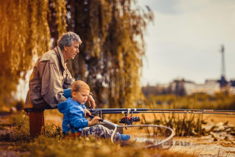 Farfar med en sonson på fiske royaltyfria bilder