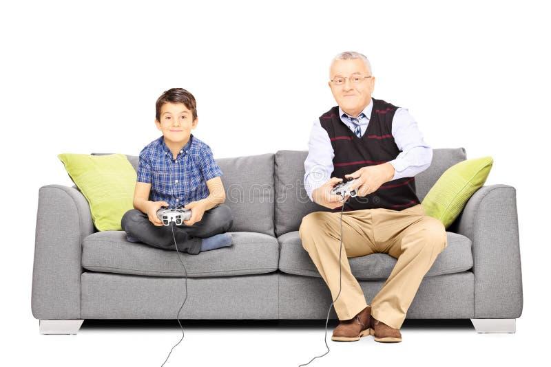 Farfar med hans brorson som placeras på en soffa som spelar videospel royaltyfri foto