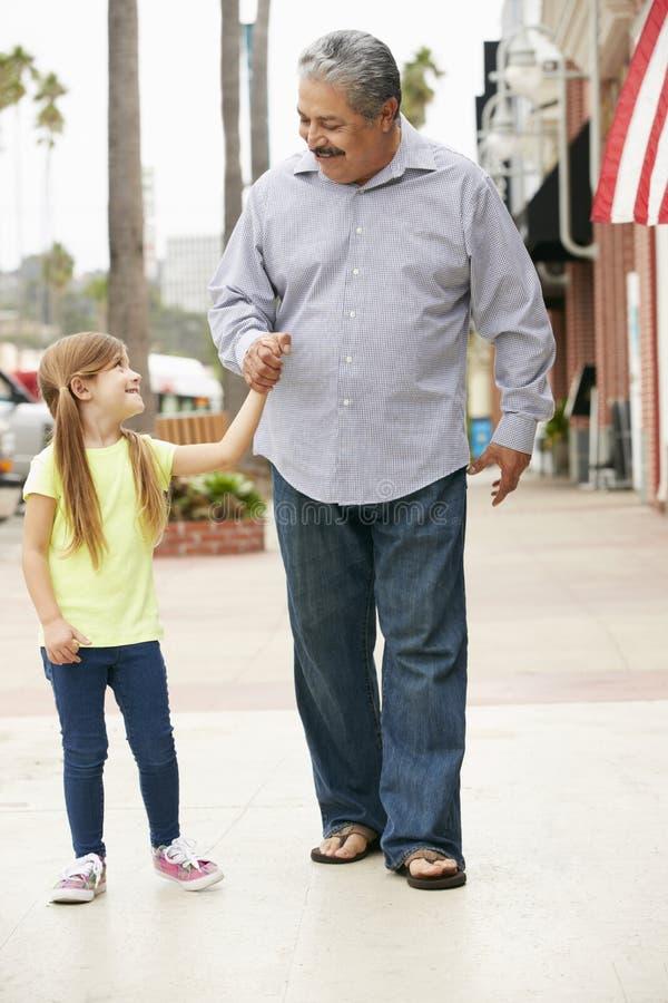 Farfar med sondottern som promenerar gatan arkivfoto