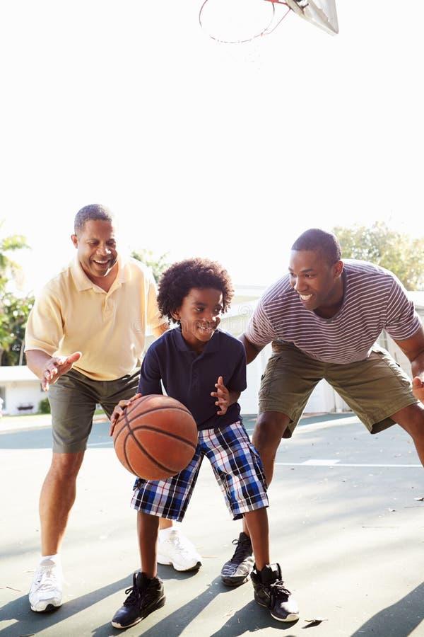 Farfar med sonen och sonsonen som spelar basket arkivfoton