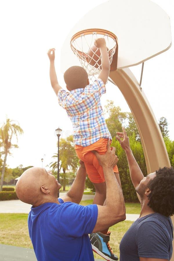 Farfar med sonen och sonsonen som spelar basket fotografering för bildbyråer