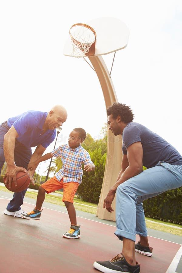Farfar med sonen och sonsonen som spelar basket royaltyfri fotografi