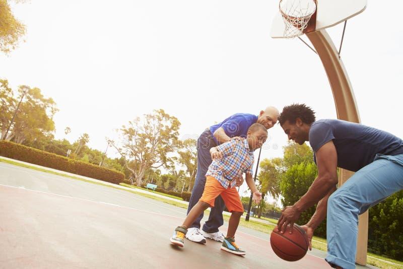 Farfar med sonen och sonsonen som spelar basket arkivfoto