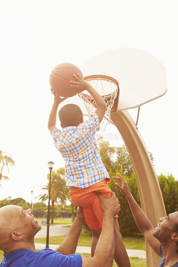 Farfar med sonen och sonsonen som spelar basket arkivbilder