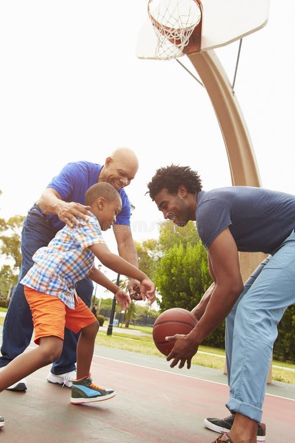 Farfar med sonen och sonsonen som spelar basket arkivbild