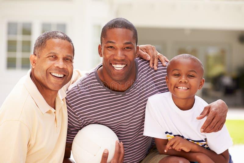 Farfar med sonen och sonsonen som spelar volleyboll arkivbilder