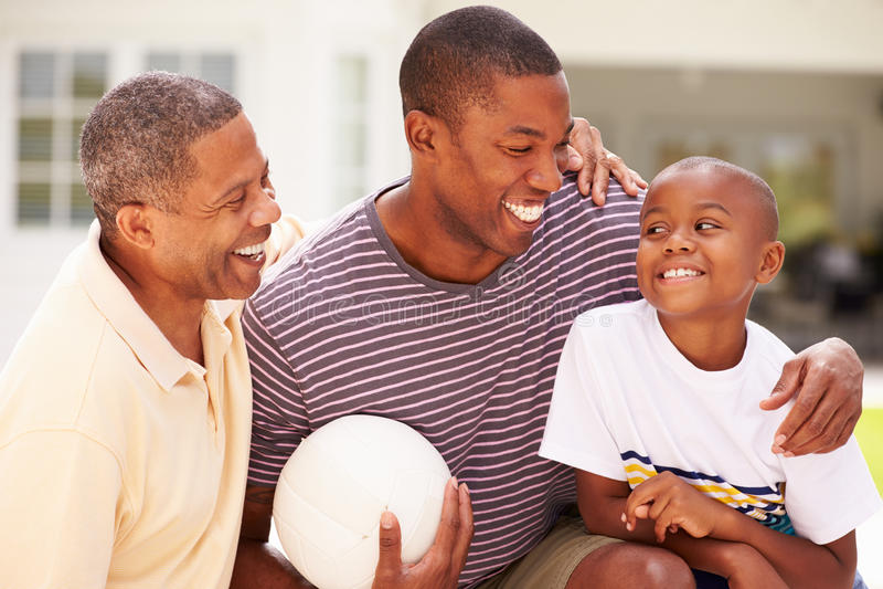 Farfar med sonen och sonsonen som spelar volleyboll arkivbild