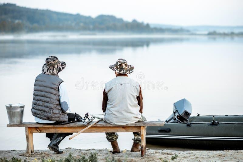 Farfar med sonen som tillsammans fiskar fotografering för bildbyråer