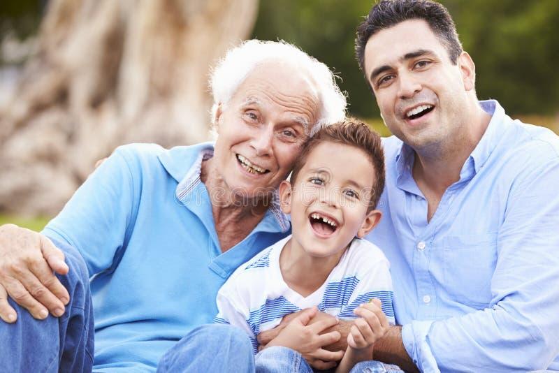 Farfar med sonsonen och fadern In Park arkivfoton