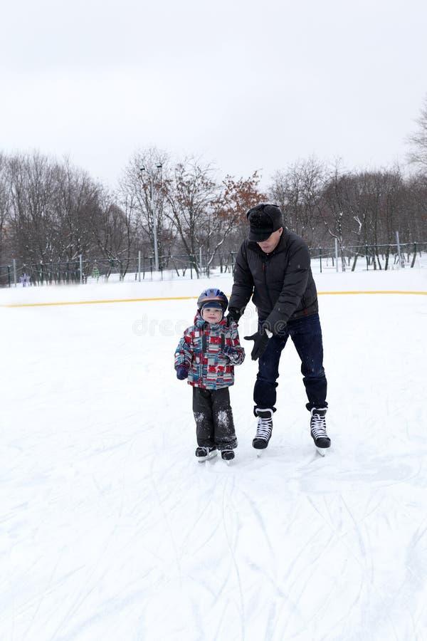 Farfar med sonsonen på den åka skridskor isbanan royaltyfria bilder
