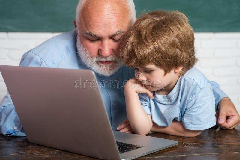 Farfar med sonsonen som tillsammans lär kurs Utbildning och lära folkbegrepp - liten studentpojke och royaltyfri fotografi