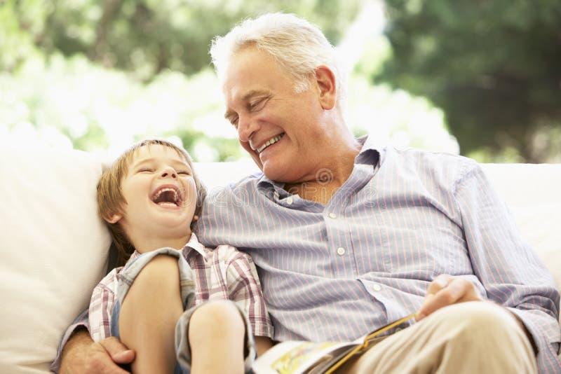 Farfar med sonsonen som tillsammans läser på soffan arkivfoto