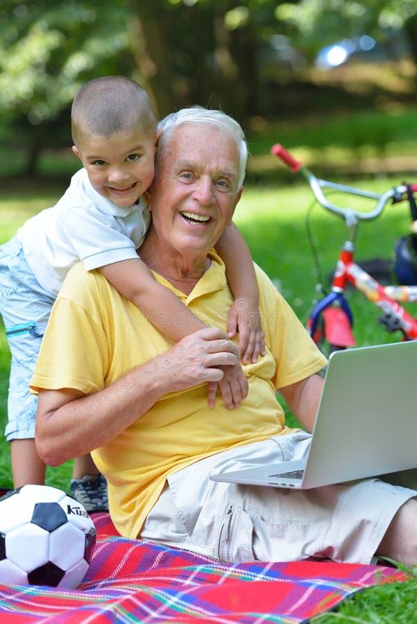 Farfar och barn som använder bärbara datorn fotografering för bildbyråer
