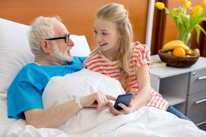 Farfar och barn som använder smartphonen fotografering för bildbyråer