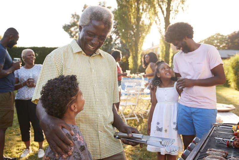 Farfar och farsa som talar med ungar på en familjgrillfest fotografering för bildbyråer