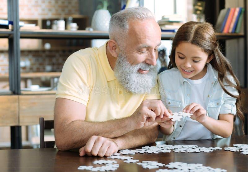 Farfar och flicka som pratar, medan spela pusslet arkivbild