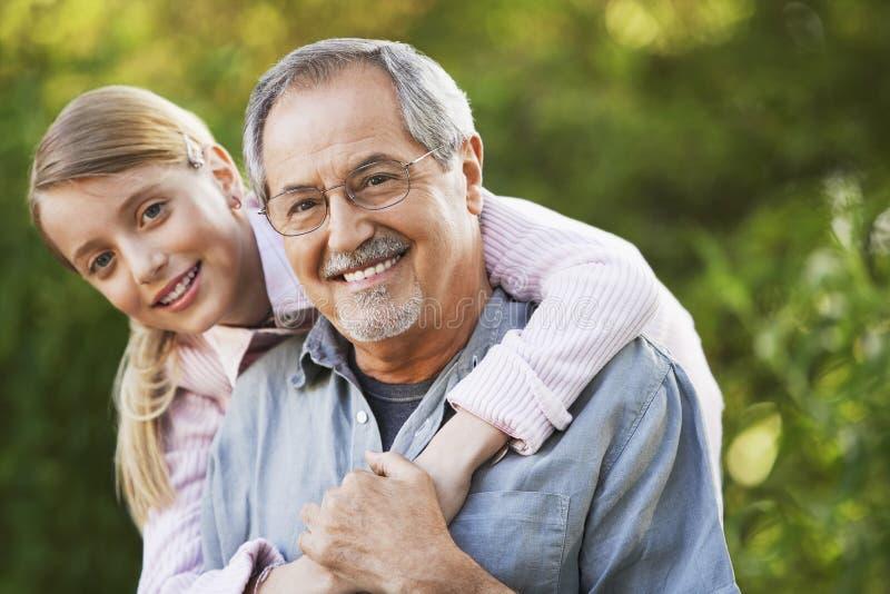 Farfar och sondotter i trädgård arkivfoton