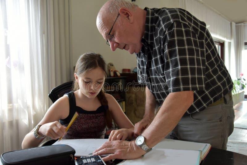 Farfar och sondotter, privat matematikhandledning fotografering för bildbyråer