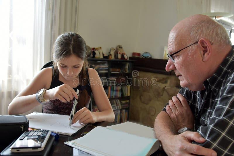 Farfar och sondotter, privat matematikhandledning royaltyfri foto