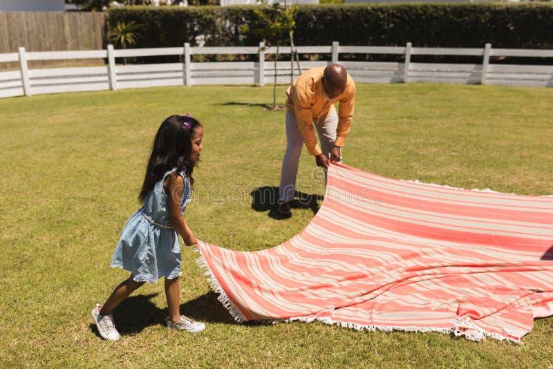 Farfar och sondotter som förlägger picknickfilten i trädgården royaltyfria bilder