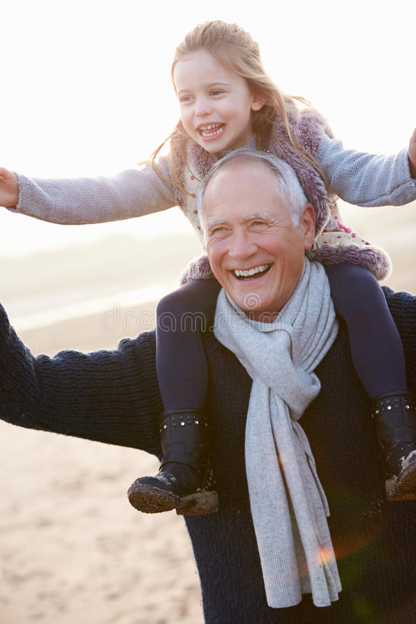 Farfar och sondotter som går på vinterstranden royaltyfri foto