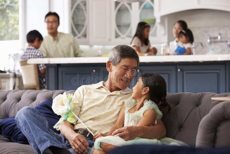 Farfar och sondotter som kopplar av på Sofa At Home arkivbild
