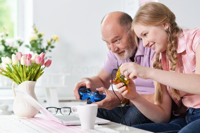 Farfar och sondotter som spelar videospel royaltyfri foto
