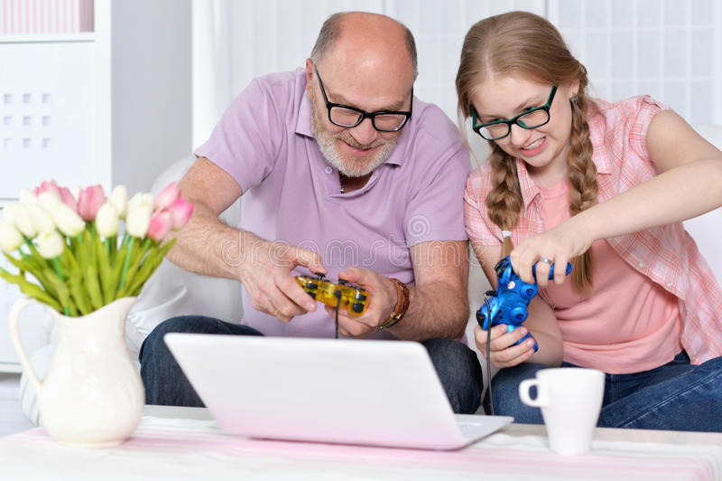 Farfar och sondotter som spelar videospel arkivfoto