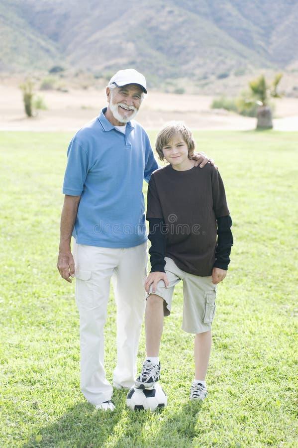 Farfar och sonson med fotboll royaltyfri foto
