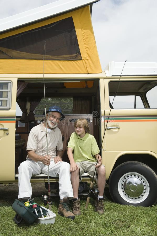Farfar och sonson med metspön i Campervan royaltyfria foton