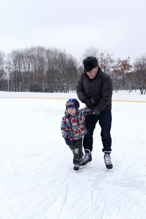 Farfar och sonson på den åka skridskor isbanan arkivfoton