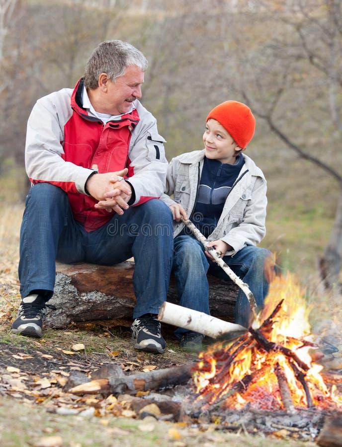 Farfar och sonson runt om en campfire royaltyfria bilder