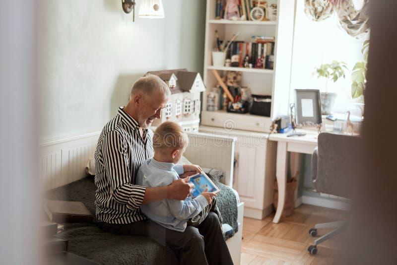 Farfar och sonson som använder den digitala minnestavlan, medan sitta på soffan arkivfoto